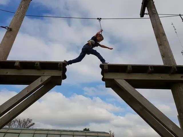 leaping across the high rope course