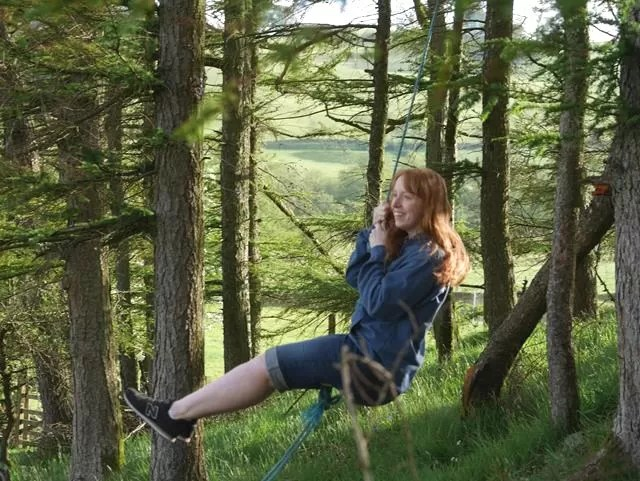 red head on rope swing in woods