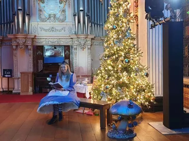 alice in wonderland sat next to christmas tree