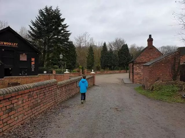 boy walking in the distance by a wall