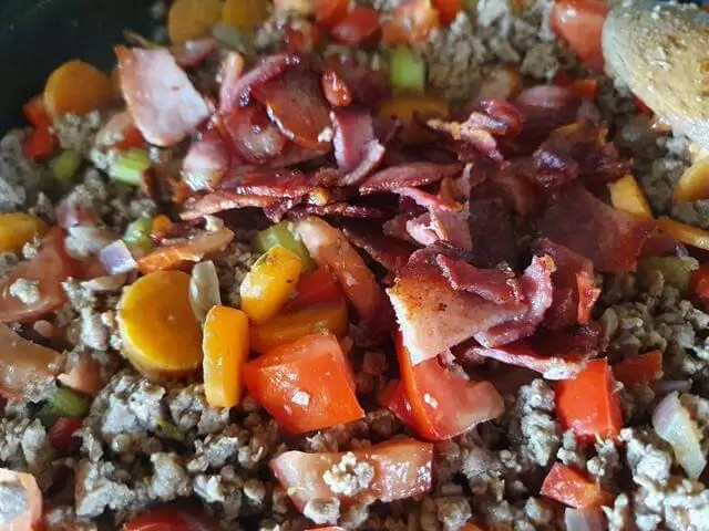 adding veg and bacon to mince