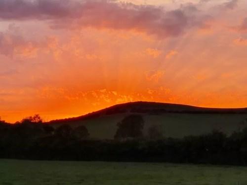 rays of sun at orange sunset over fields