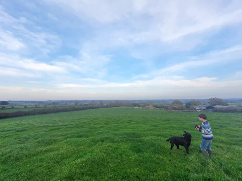 walking above our house in he countryside with the black labrador