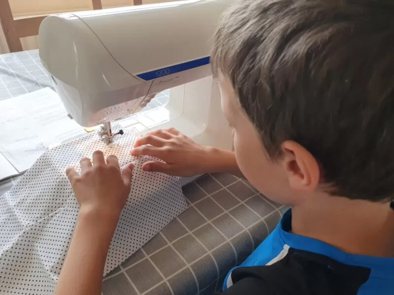 boy learning to use a sewing machine