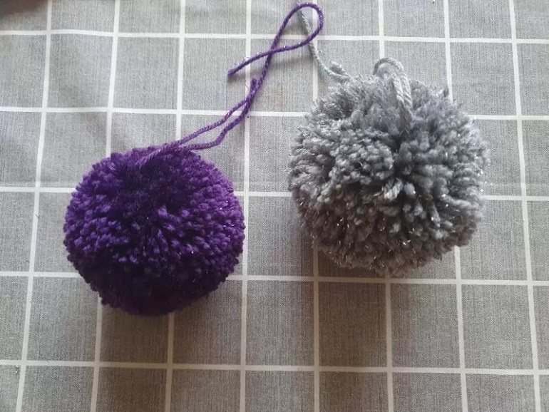purple fluffy pom pom and less fluffy silver one