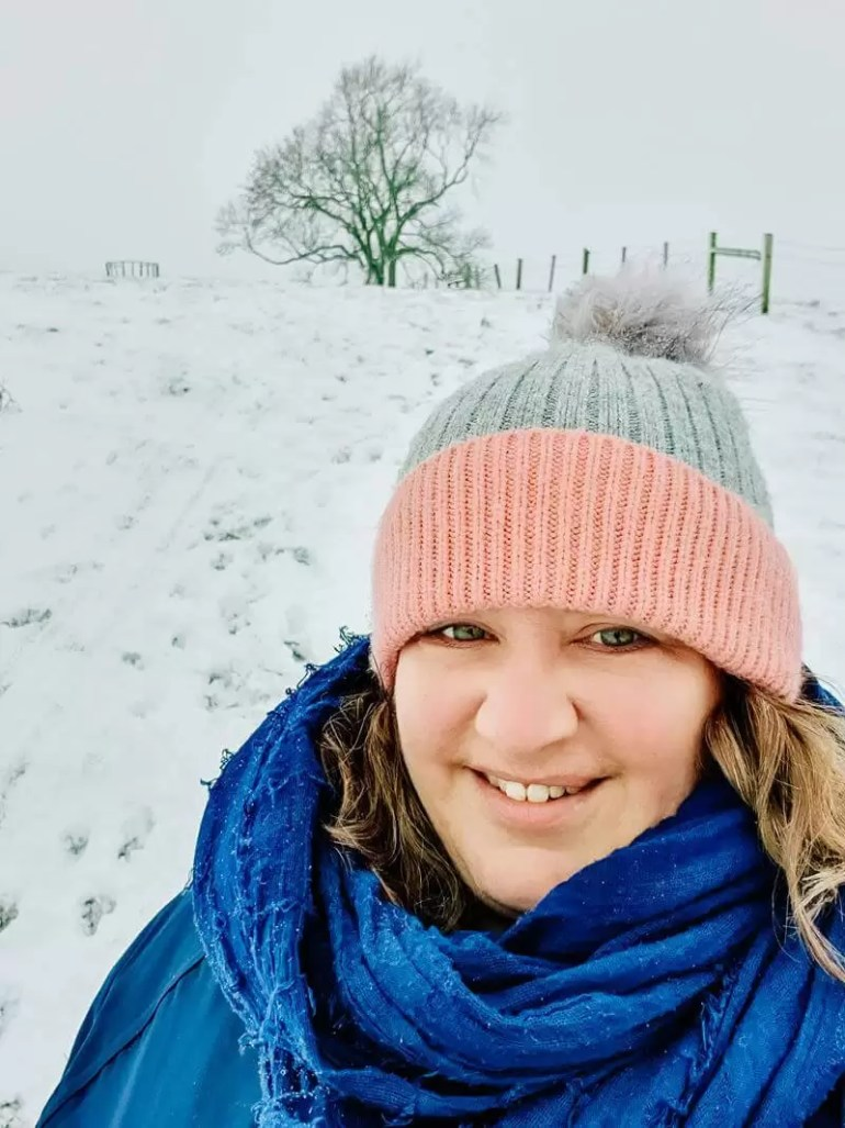 seflie of woman in pink and grey bobble hat with big blue scarf in the snow