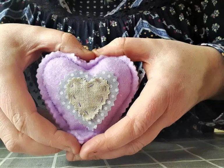 hands holding stuffed pretty felt heart in a heart shape