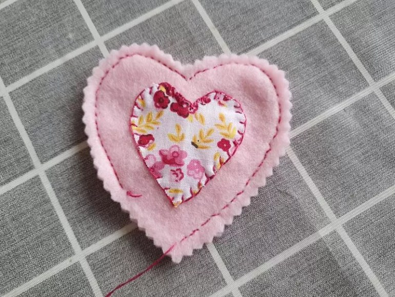 pink heart stitched with appliqued flower fabric heart on