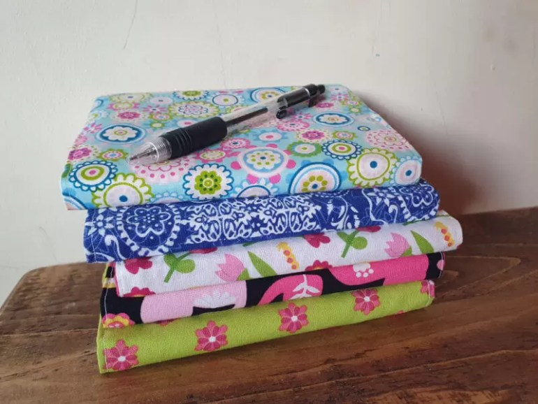 pile of finished fabric covered notebooks