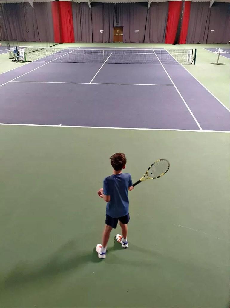 boy standing on edge of indoor tennis court