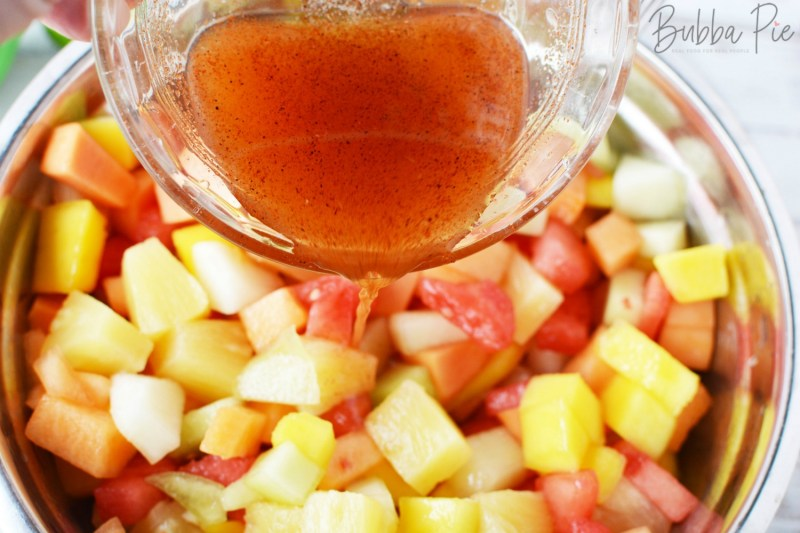Pour the chili lime sauce into the Mexican Fruit Bowl to toss it.