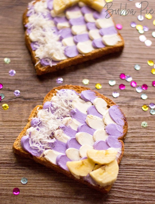 Easy Mermaid Toast with coconut and banana sitting on a wooden table with fun decorations