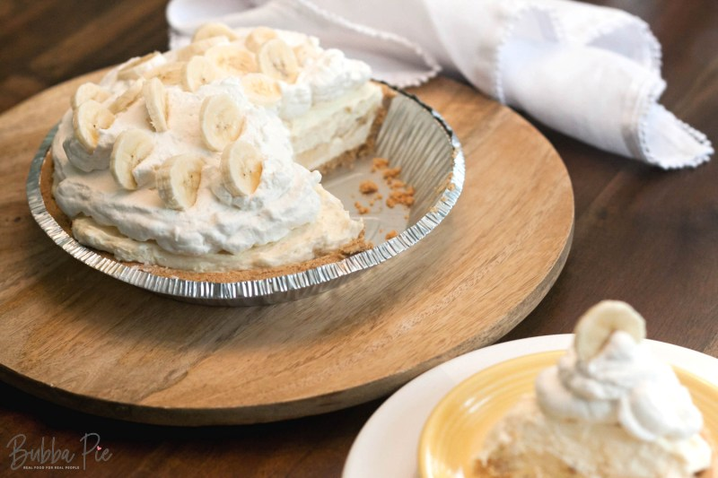 Easy No Bake Banana Cream Pie slice sitting on a plate with fresh bananas and whipped cream on top.