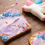 Unicorn Toast Laying on a table with sprinkles and a toy unicorn