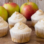 Apple Cinnamon Cupcakes with Buttercream Frosting sitting on a table with fresh apples makes a great thanksgiving dessert