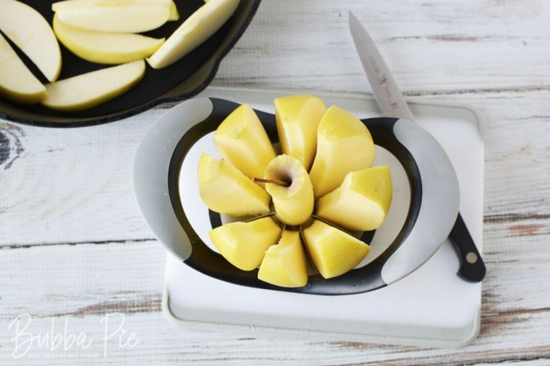 an apple being sliced by an apple slicer/corer on a cutting board with a knife