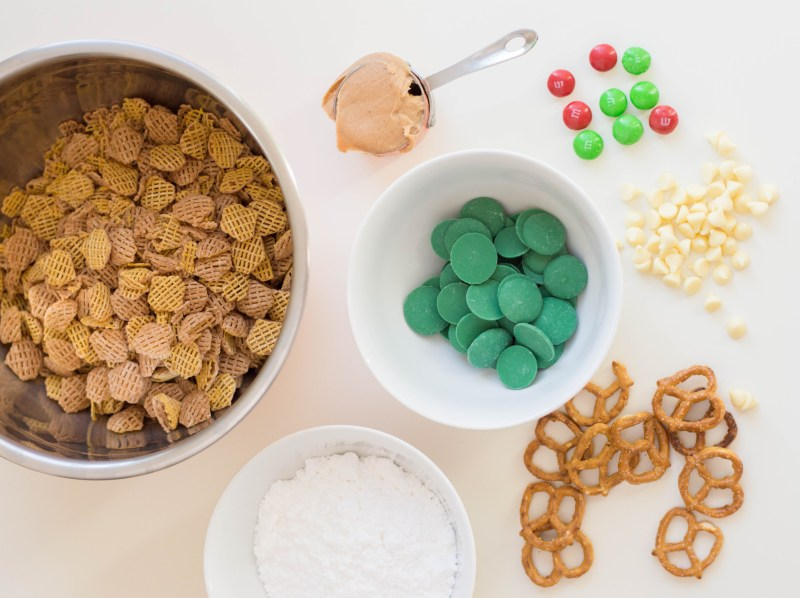 Christmas Puppy Chow Ingredients include green candy melts, powdered sugar, butter and peanut butter