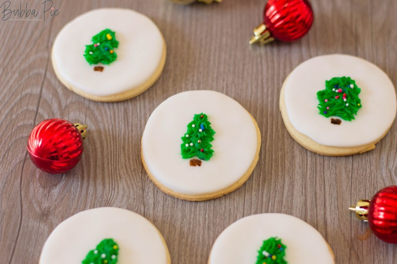 Christmas Tree Sugar Cookies sitting on table with ornaments