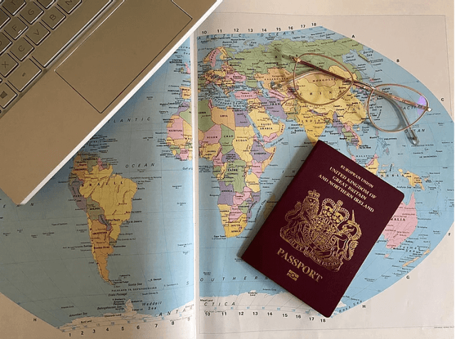 Passport, global map and a laptop are prepared for going to the destination