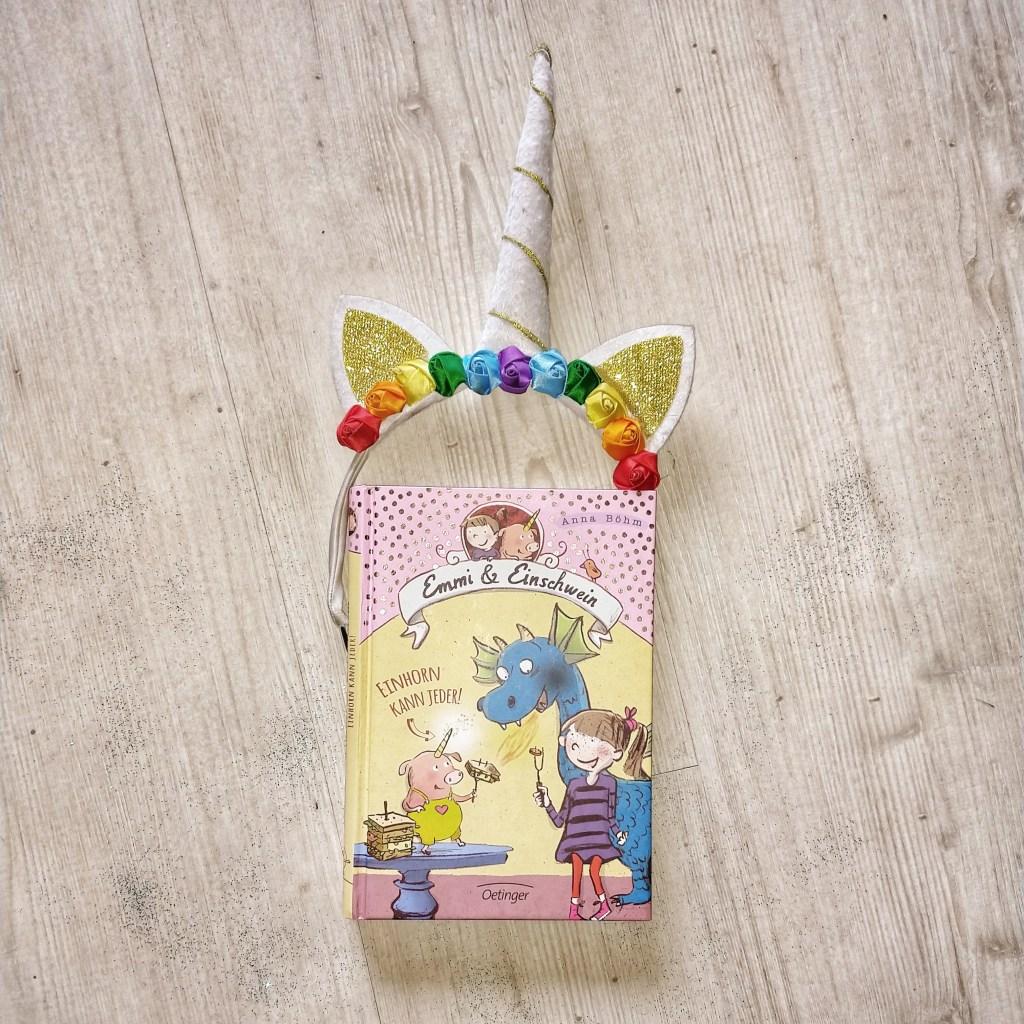 """Das Buch """"Emmi und Einschwein - Einhorn  kann jeder"""" von Anna Böhm auf einem weißen Holzboden. Oben umrahmt ein Eihornhaarreif mit Horn Blumen und glitzernden Ohren das Buch, rundherum ist türkiser Glitzer verstreut."""