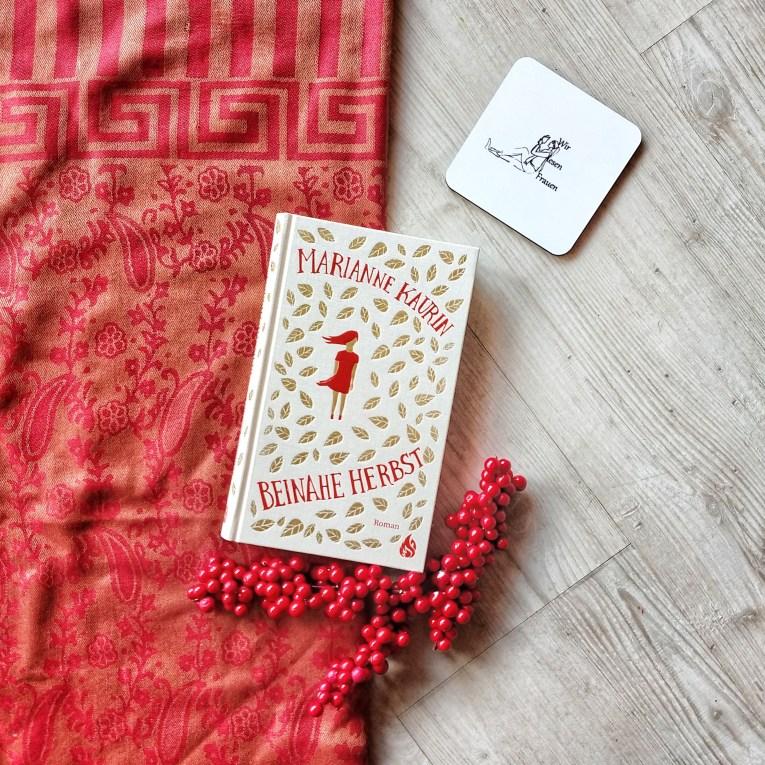 Auf einem Hintergrund, der halb aus hellem Holz, halb aus einem roten, mit Blumen verzierten Stoff besteht, liegt das Buch. Unten liegen rote Früchte, oben rechts ein #WirlesenFrauen Untersetzter. Das Cover des Buches zeigt ein Mädchen mit roten, vom Wind verwehten Haaren, und rotem, verwehten Kleid. Ring herum fallen goldene Blätter.