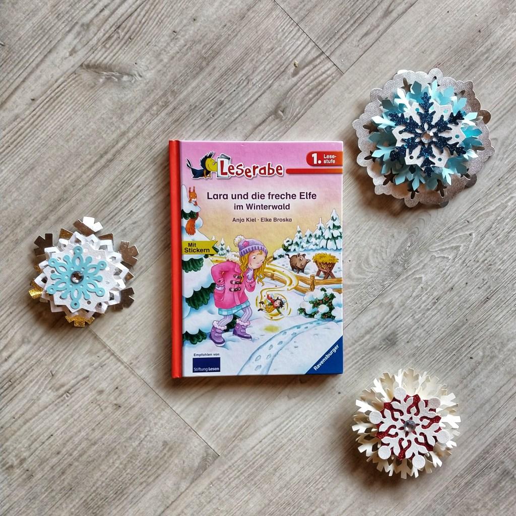 Lara und die freche Elfe im Winterwald zeigt Lara, ein kleines blondes Mädchen mit rosa Jacke im eingeschneiten Winterwald, hinten steht ein Wildschwein und neben Lara schwebt die freche Elfe Fritzi.