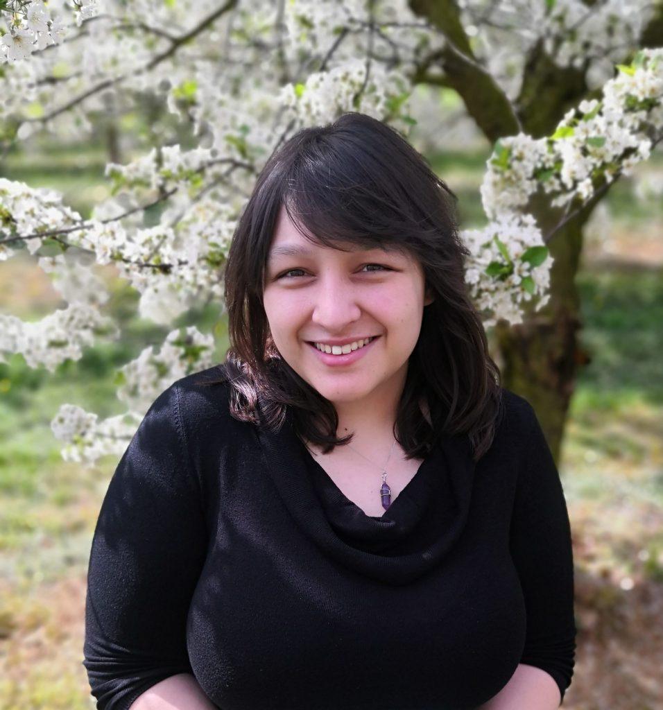 Jana Tomy, schwarze, halblange Haare, vor einem weiß blühenden Baum