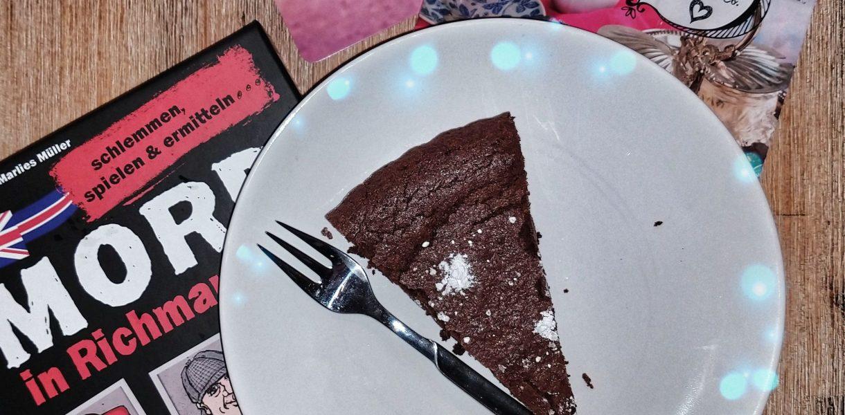Die Verpackung des Krimi-Dinners Mord in Richman Hall neben einem Stück Schokoladen Tarte auf einem Teller und dem Kochbuch zum Spiel