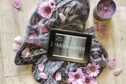 Der Kindle zeigt das Cover von Milchmann in schwarz-weiß. Das Gerät liegt auf einem Schal auf einem hellem Holzboden, darum rosa Blüten und eine lila Kerze