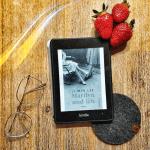 """Auf einem Holztisch liegt ein eReader, daneben eine Brille, oben drei Erdbeeren. Auf dem Reader sieht man in schwarz-weiß das Cover von """"Marilyn und ich"""" von Ji-Min Lee. Es zeigt die beine und Füße zweier Personen mit Rock und hochhackigen Schuhen, einer der Personen sitzt, die andere steht."""