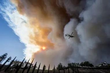 Un helicóptero lanza agua para extinguir los incendios forestales en Paradise