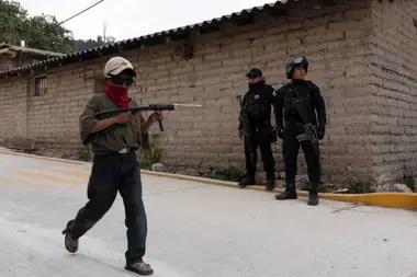 Reinel Toribio, de 9 años, pasa junto a oficiales de la policía estatal con una pistola de juguete