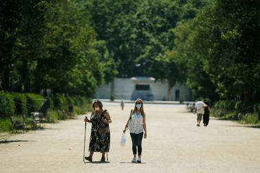 Dos mujeres con máscaras faciales caminan en el parque de la Ciudadela durante las horas permitidas por el gobierno para hacer ejercicio en Barcelona el 30 de mayo de 2020 a medida que el país comienza a aflojar un cierre nacional para evitar la propagación del nuevo coronavirus