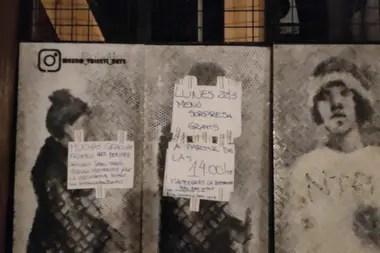 Adrián pega carteles en la puerta de su local para anunciar las novedades