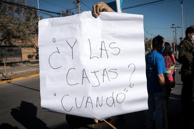 Un manifestante sostiene un cartel pidiendo cajas de ayuda durante una protesta contra el gobierno del presidente chileno Sebastián Piñera en medio de la pandemia de coronavirus, en Santiago, el 25 de mayo de 2020