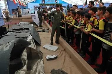 Un miembro de la Guardia Revolucionaria de Irán muestra a un grupo de niños, los restos de un drone Global Hawk estadounidense derribado por fuerzas iraníes en el Estrecho de Ormuz