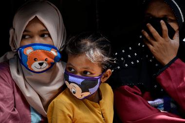 Mujeres y niñas utilizan un barbijo en Indonesia en plena pandemia de coronavirus