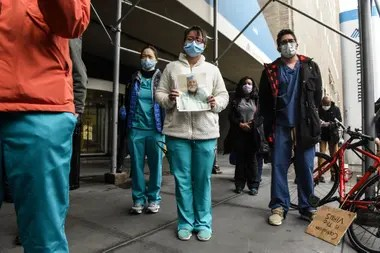 Médicos y enfermeros del hospital Mount Sinai muestran fotos de sus colegas fallecidos y ruegan que les envíen más suministros para protegerse