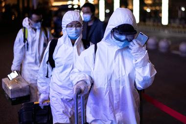 Los pasajeros usan trajes especiales en la estación de tren Wuhan Wuchang para abandonar la ciudad en la provincia central de Hubei de China a principios del 8 de abril de 2020