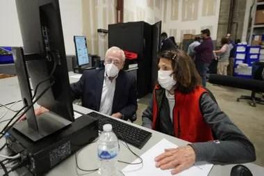 Representantes demócratas y republicanos revisan las boletas de voto ausente en el Centro de preparación de elecciones del condado de Fulton, ayer, en Atlanta, Georgia