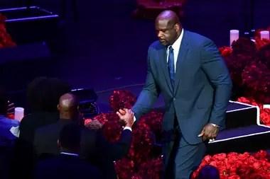 Dos potencias se saludan: Michael Jordan (sentado) y Shaquille ONeal chocan sus manos derechas; el motivo que los reúne no da como para sonrisas.