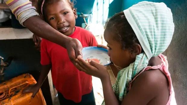 Una chica toma agua en Madagascar