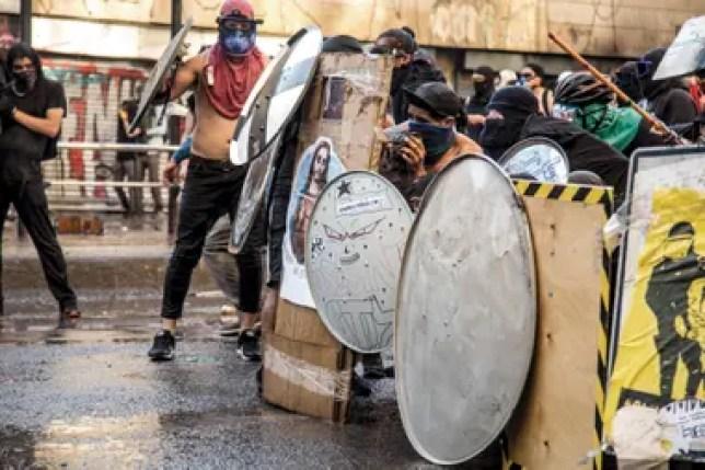 Los manifestantes se protegen de los gases lacrimógenos y los balines que disparan los carabineros