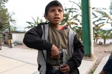 Miguel Toribio, de 11 años, pone una pistola que pertenece a su padre en su cinturón
