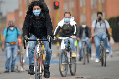 Las personas usan mascarillas como medida preventiva contra la propagación del nuevo coronavirus, mientras andan en bicicleta en Bogotá, el 29 de abril de 2020