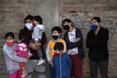 Una familia observa cómo los trabajadores municipales desinfectan un barrio de Santiago, el 16 de mayo de 2020, en medio de la cuarentena total obligatoria debido a la pandemia de coronavirus