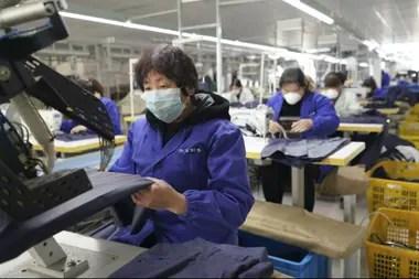 Trabajadores con barbijos en un taller textil de Pekín