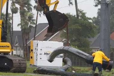 Un trabajador maniobra una sección de una tubería mientras una cuadrilla trabajaba para instalar bombas de drenaje en el oeste de Morgan