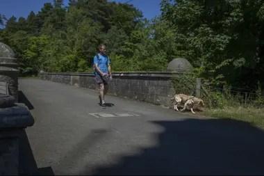 Un hombre lleva su perro con correa sobre el misterioso puente Overtoun en Dumbarton, Escocia