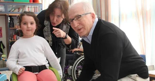 Kaplan junto a una de las niñas que recibió la silla